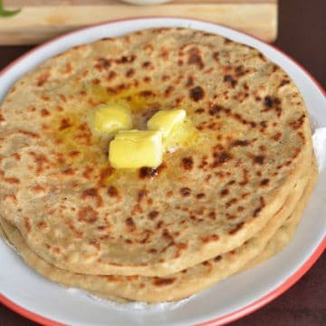 aloo paratha served in a plate with butter and curd.