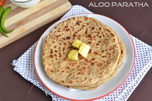 Aloo paratha served with butter in a white plate.