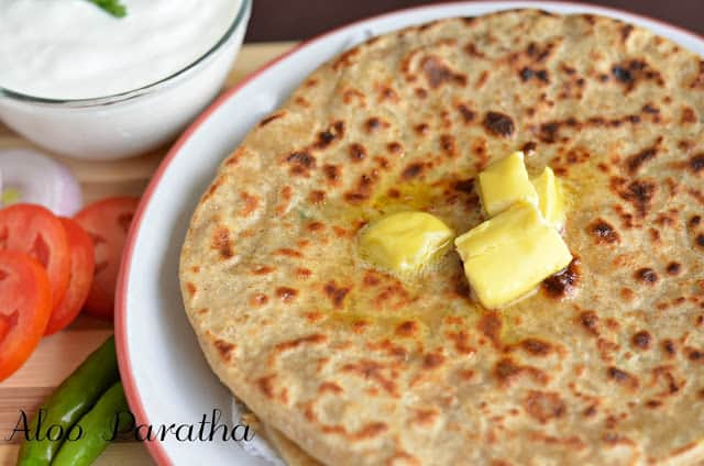 a closeup click of aloo paratha with butter & curd.