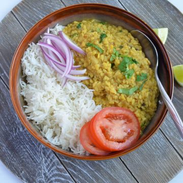 white urad dal and rice served in a grey bowl with cut onions and sliced tomato.