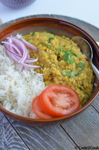 white urad dal and rice served in grey bowl with cut onion and tomato.