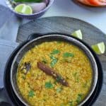 white urad dal tadka served in black bowl with lemon wedges.