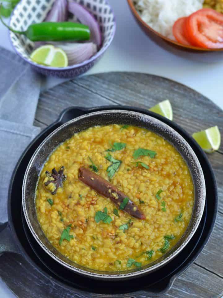 white urad dal tadka served in black bowl with lemon wedges.
