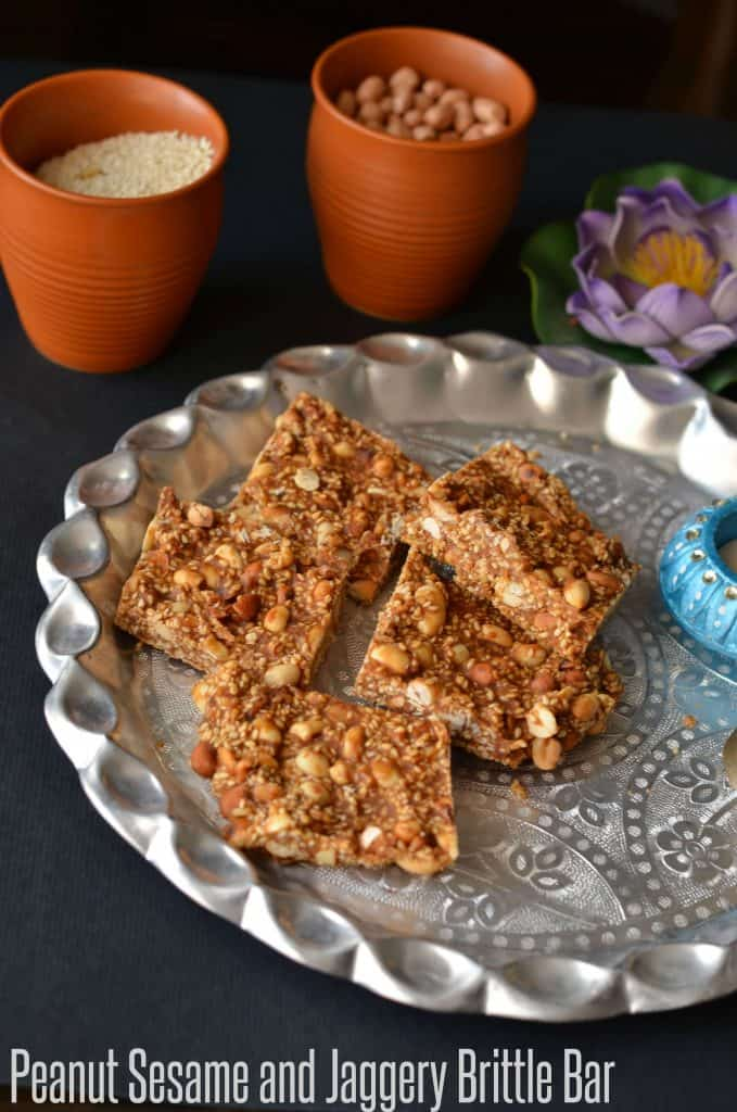 close up click of til peanut chikki in serving plate. peanut and sesame are kept in utensils around the plate.
