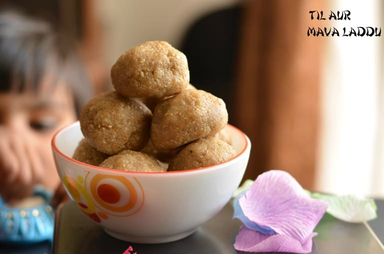 til mawa ladoo is clicked from left side. It is served in glass bowl and kept over baking pan.