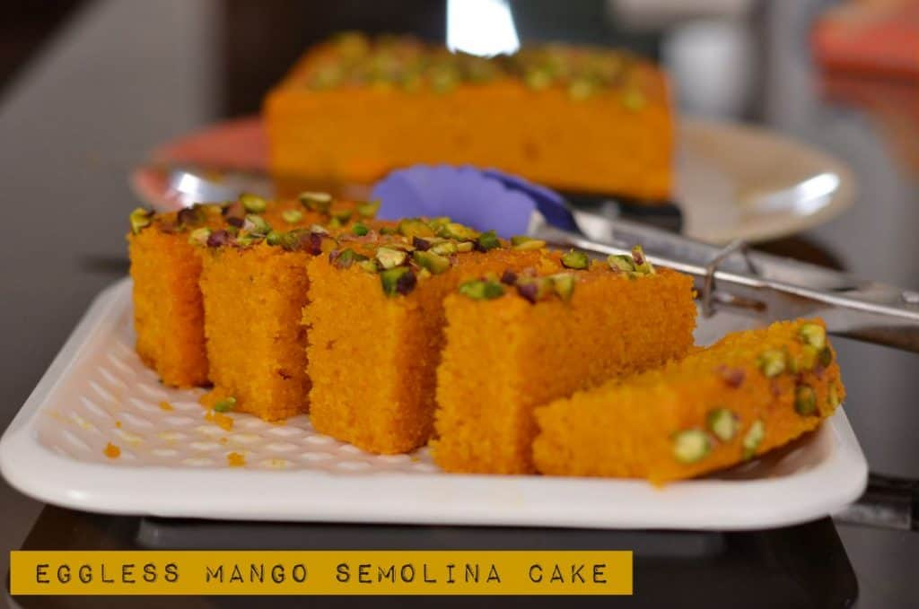 Eggless mango semolina cake is super easy to prepare.  This cake is moist, dense in texture and so aromatic with its delicious mango flavor. Mango pulp folded with semolina, cardamom, and few handful nuts gives you chewy experience with every bite.  A perfect cake to bake in mango season and you can never go wrong with it.