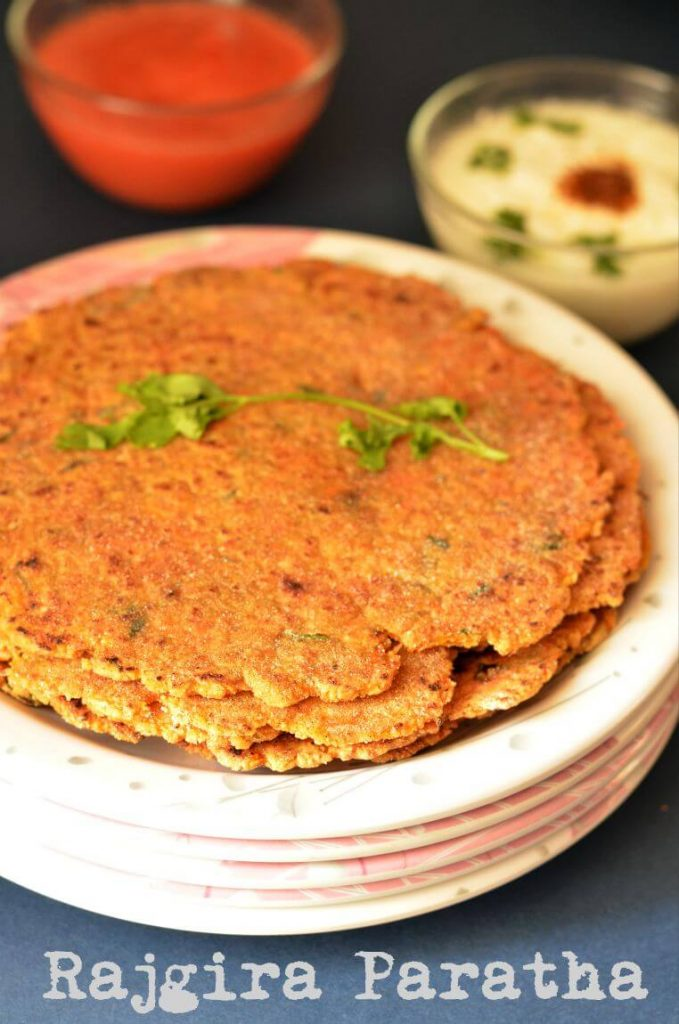 Rajgira paratha with vegetables served in a stack of plates. Coriander leaf is placed over them.