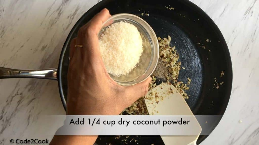 adding desiccated coconut & cardamom powder to the mixture