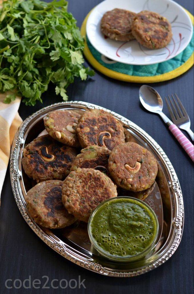 Kuttu ki Tikki or buckwheat cutlets are served with coriander chutney in a silver plate.