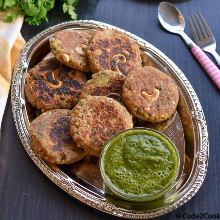 kuttu ki tikki or buckwheat cutlets served with green chutney in a oval shaped plate.