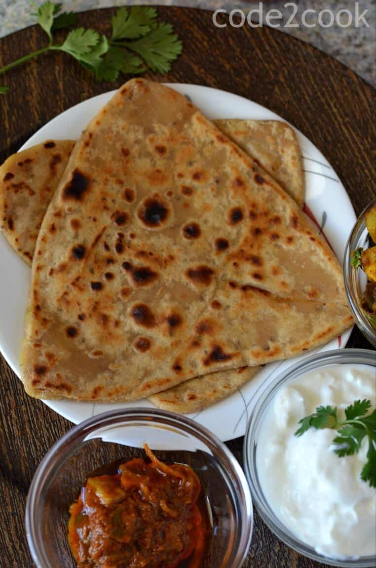 A close up of Ajwain paratha served with pickle & curd