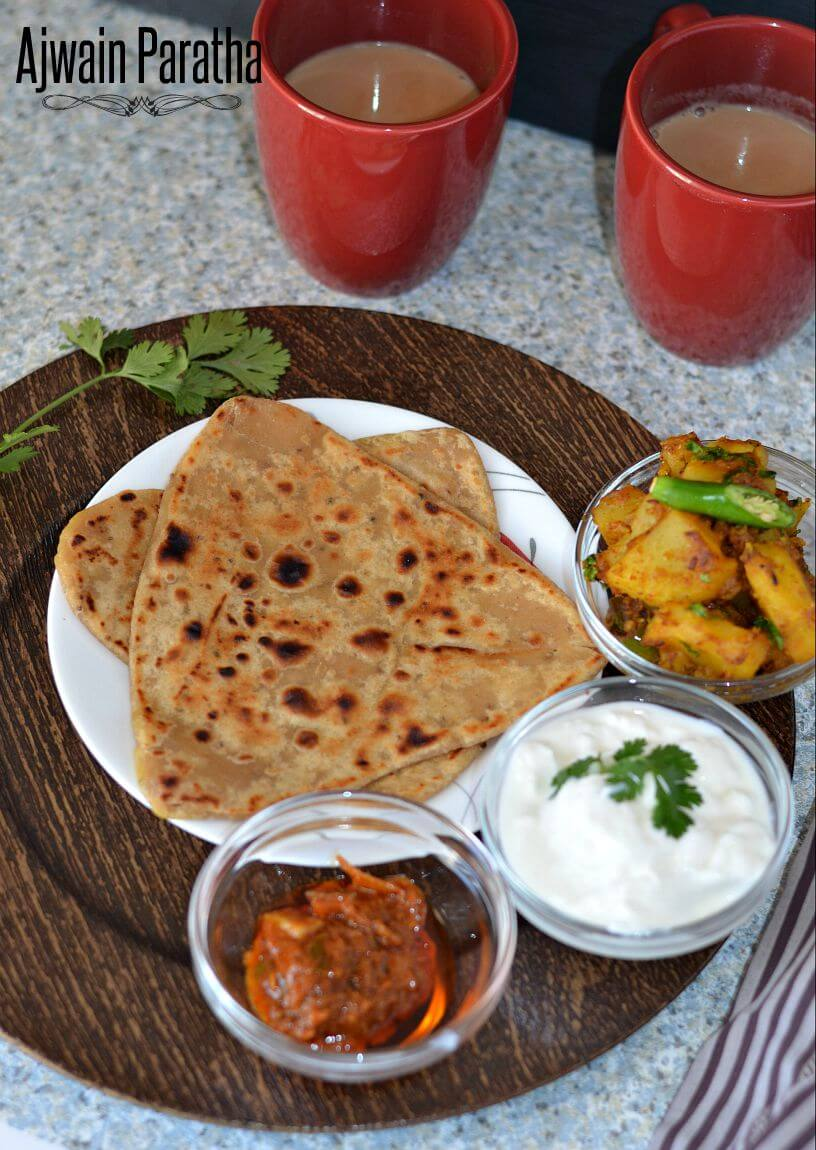 Ajwain ka paratha served with pickle, curd & potato curri. Masala chai cups are alongside.