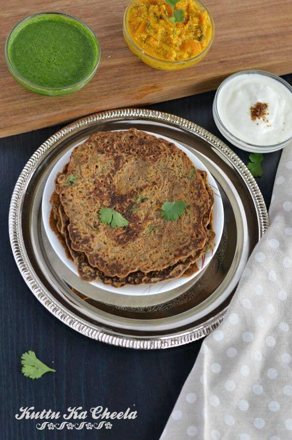 Kuttu ka cheela or falahari cheela served on golden plate with vrat ki chutney, plain curd and vrat ki sabji.