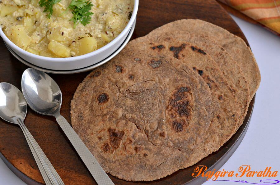 Amarnath flour paratha is served with vrat ke aloo on a wooden board. Spoons are kept around it.