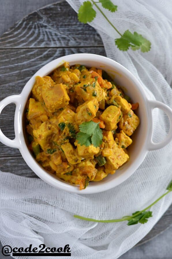 vegan sana thongba or vegan paneer curry click from up in a white serving bowl.