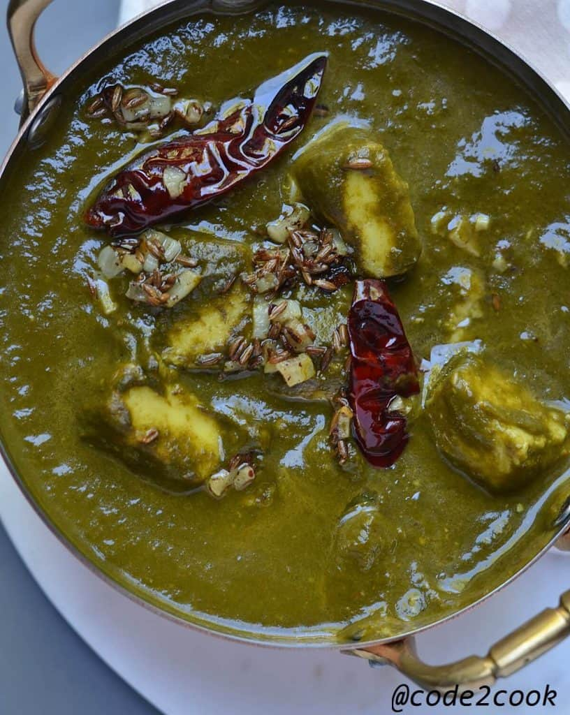 closeup of palak paneer with garlic and red chili tempering