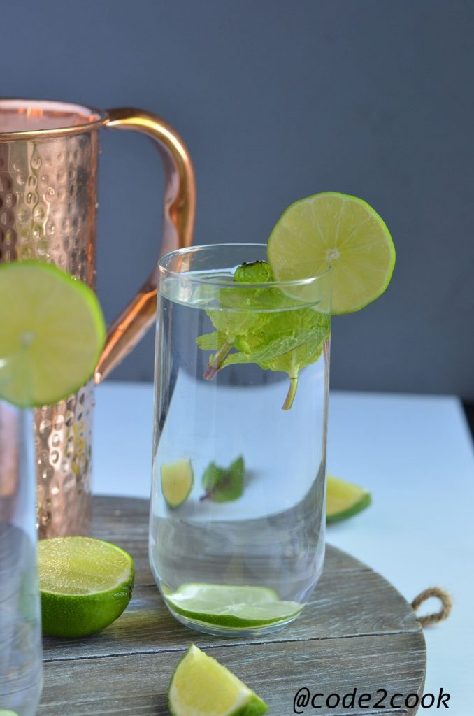 copper enriched water poured in a glass. mint leaves and lemon wedges are added.