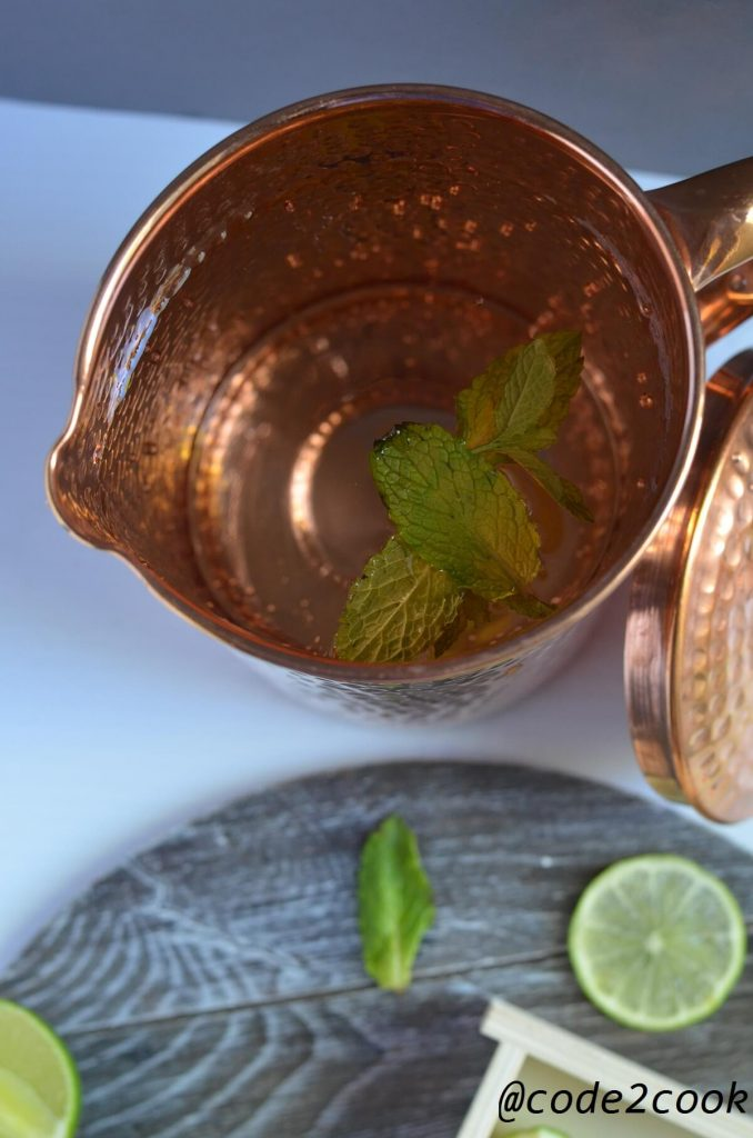 Water in the copper pitcher.Lemon wedges and mint leaves are scattered on wooden surface.