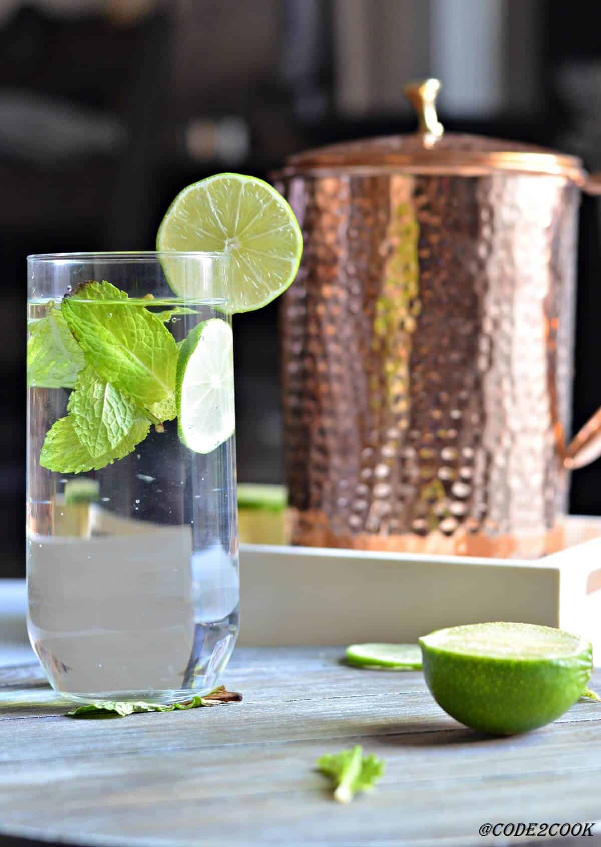 copper pitcher with a glass of drinking water served with lemon wedge & fresh mint leaves.