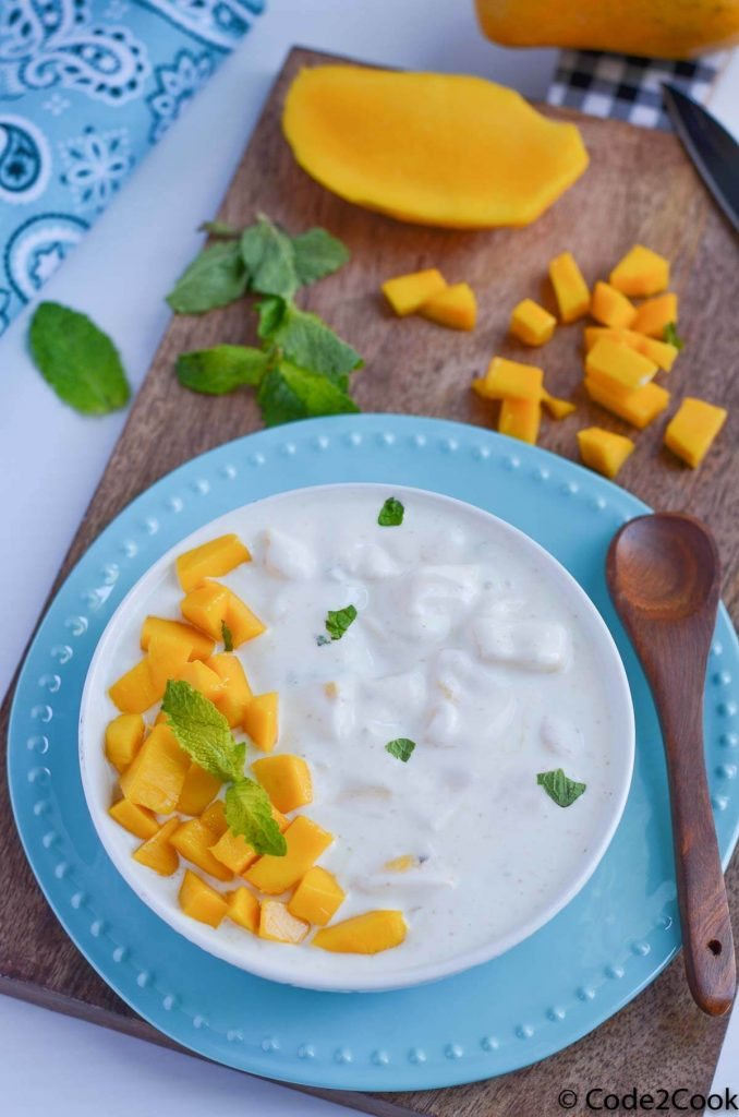 mango raita served in white bowl, garnished with mint and chopped mango. Bowl is kept over a wooden board with mint leaves and cut mango.