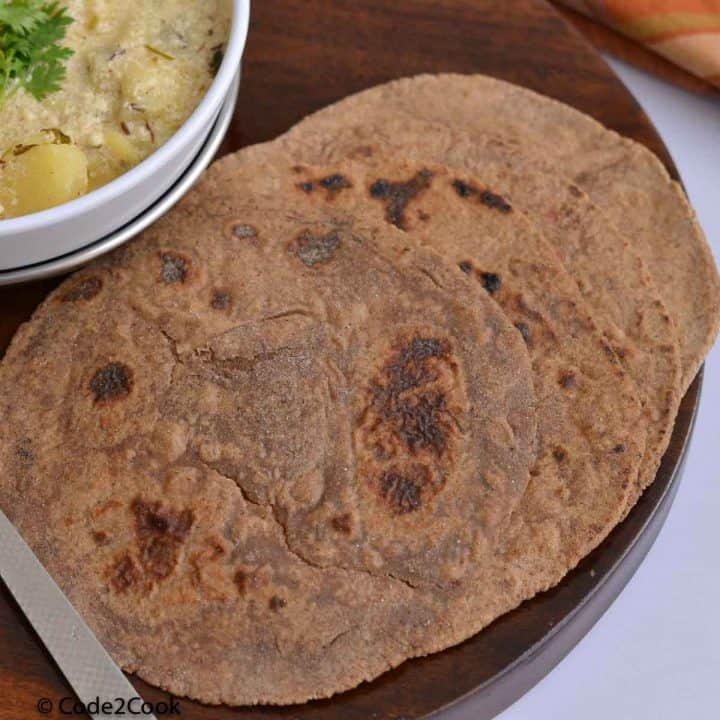 amarnath flour paratha served with dahi vale aloo on a wooden board.