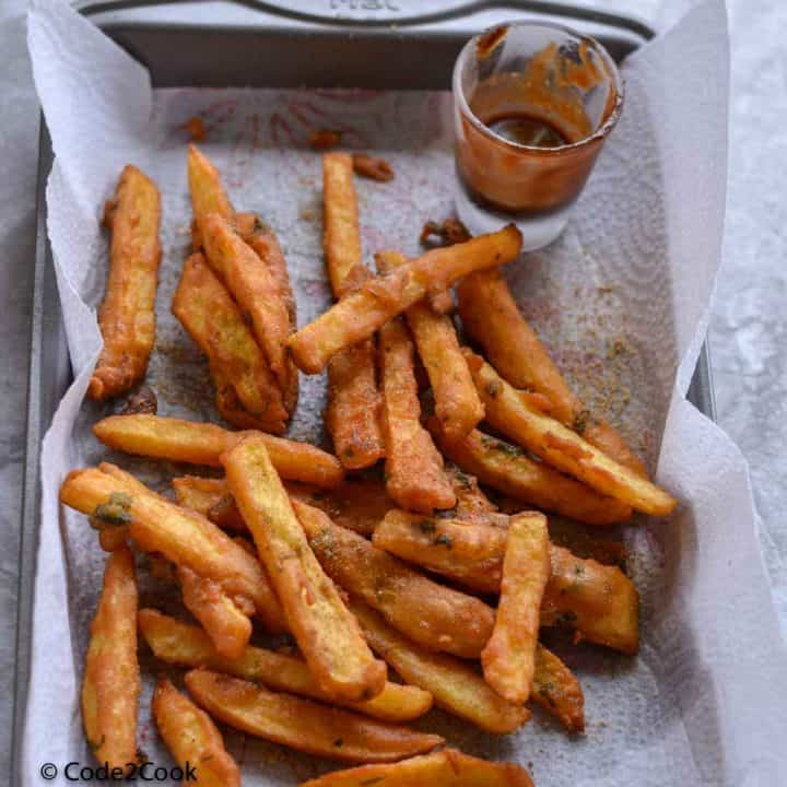 A close up click of farali french fries kept on baking pan. Tamarind chutney is also served along with fries.