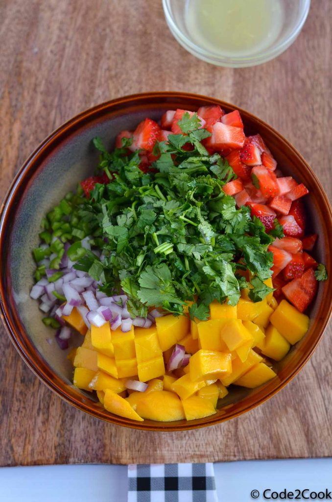 ingredients of strawberry mango salsa are in the brown bowl