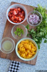 all ingredients of mango strawberry salsa are kept over wooden board.
