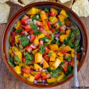 strawberry mango salsa is served in brown bowl with tortilla strips.