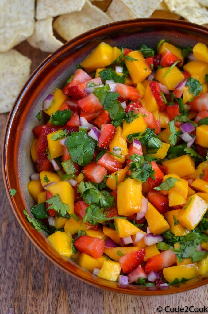 close up of Strawberry Mango Salsa served in brown bowl.