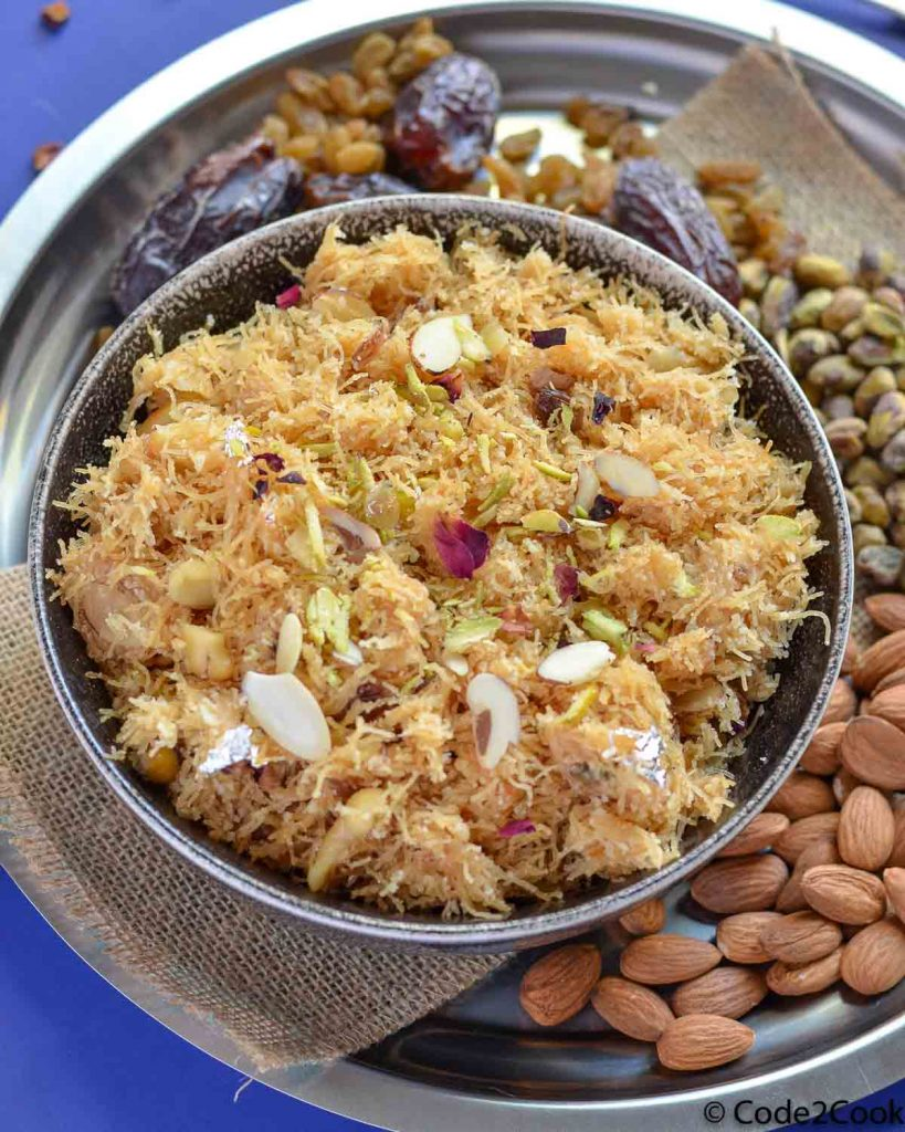 sweet vermicelli served in a grey bowl surrounded by dry fruits in a steel plate.