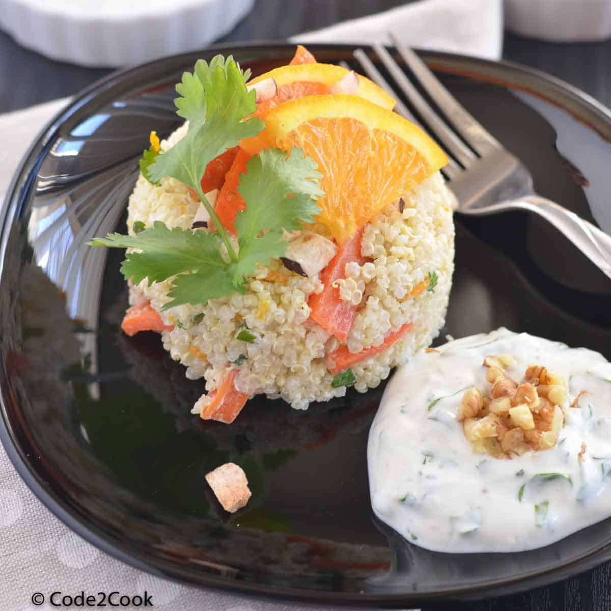 quinoa carrot salad served on a white place with tahini dressing