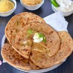 bhujia sev paratha on a plate and served with curd, namkeen.