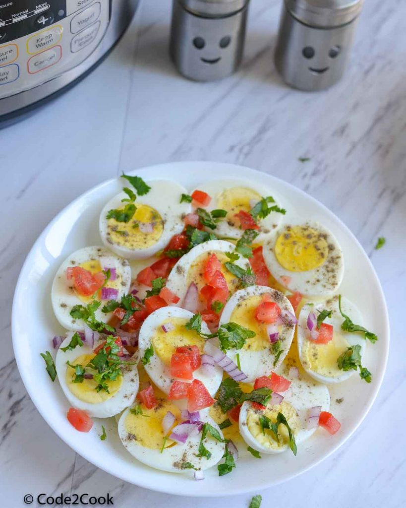 boiled eggs are served in white plate. Garnished with chopped tomato, onion and coriander. Salt & pepper sprinkled.