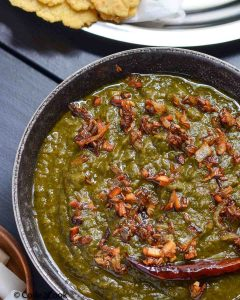 a close sarson ka saag click served in black bowl & garnished with tempering