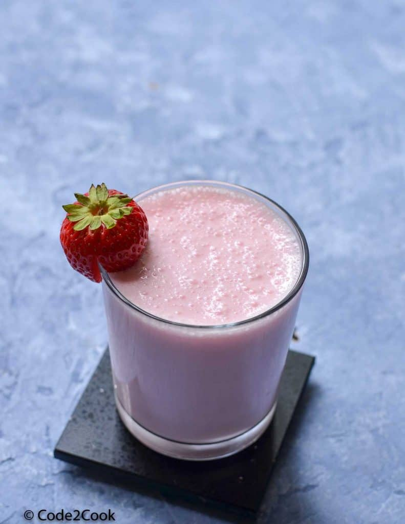 Rooh afza lassi served in a glass and garnished with strawberry