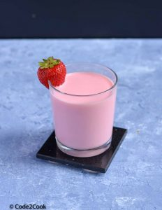 rooh afza milkshake served in a glass with strawberry