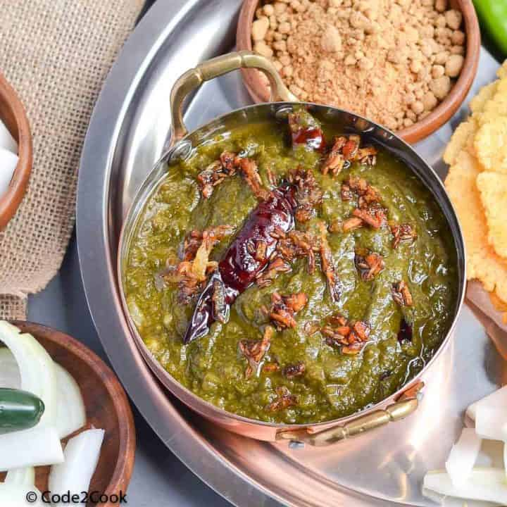sarson ka saag served in kadai with makki ki roti, radish & jagery