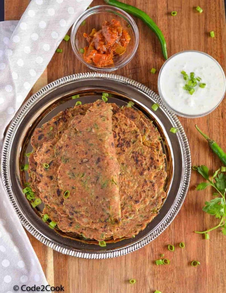 sprin onion paratha served in a plate along with curd and pickle.