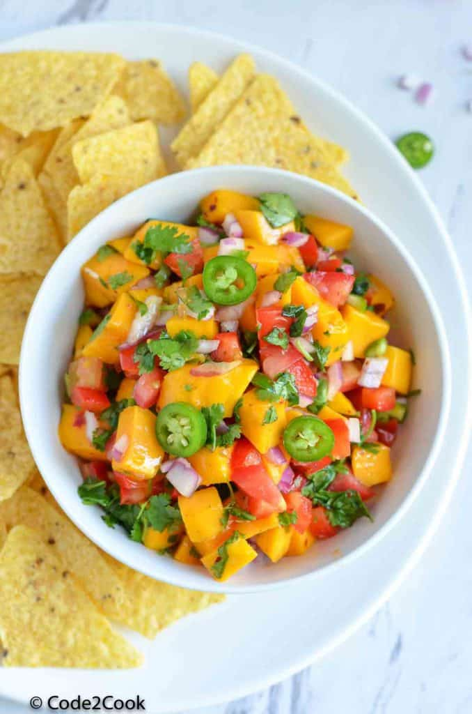 mango salsa served in white bowl with tortilla chips along side.
