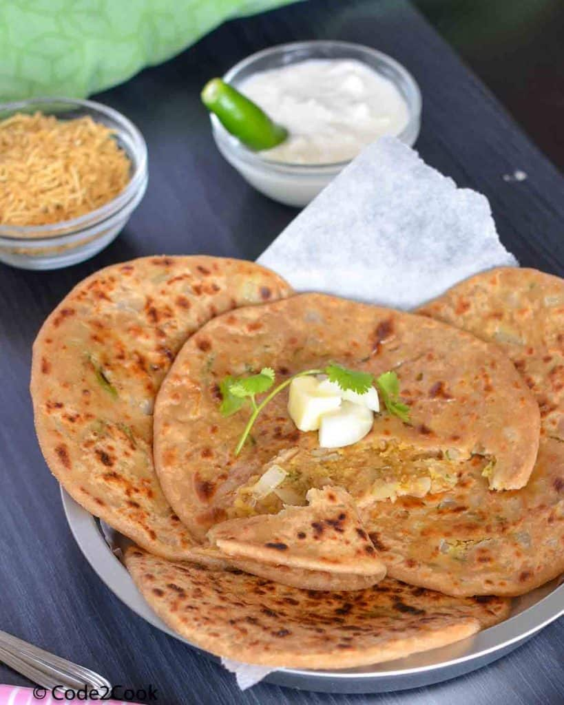 Parathas are spread on a big plate with curd & namkeen.