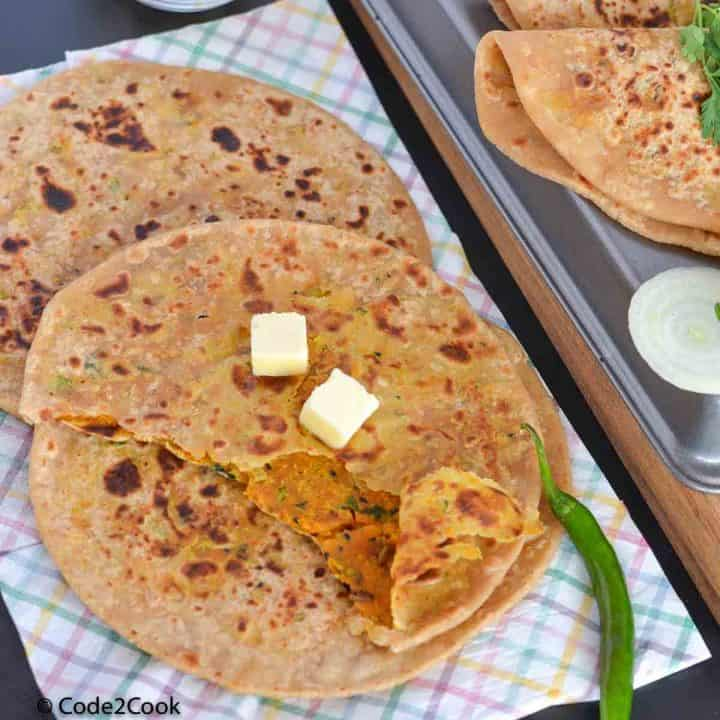 close up click of masala paratha with butter cubes