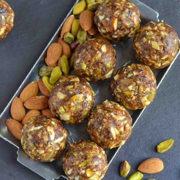 over head shot of dry fruits laddu with dates kept in a silver plate.