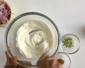 whisking yogurt with water in a glass bowl.