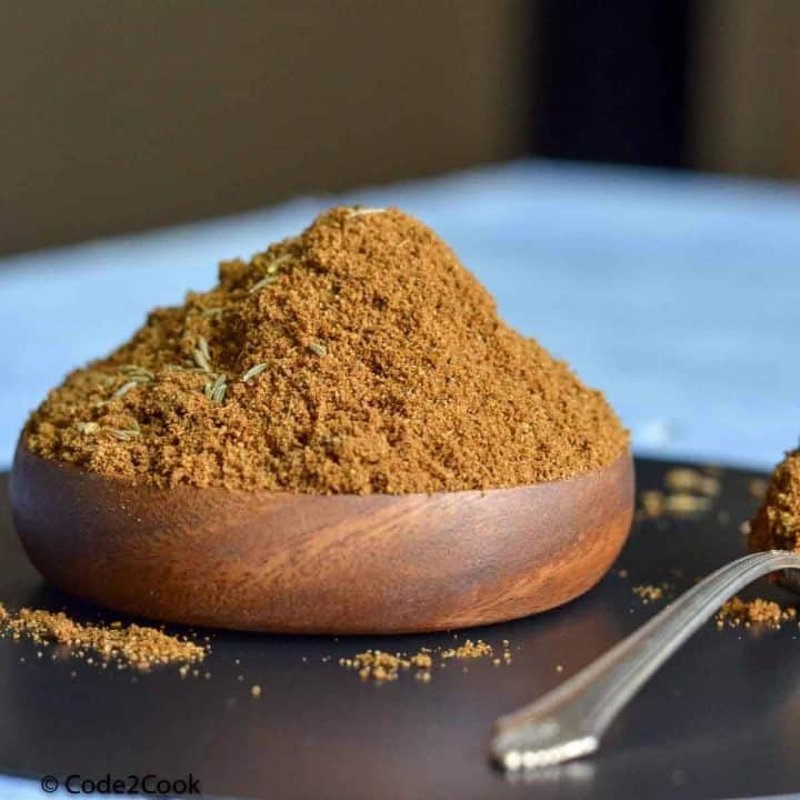 Ground cumin is kept in a wooden bowl with spoonful on right side.