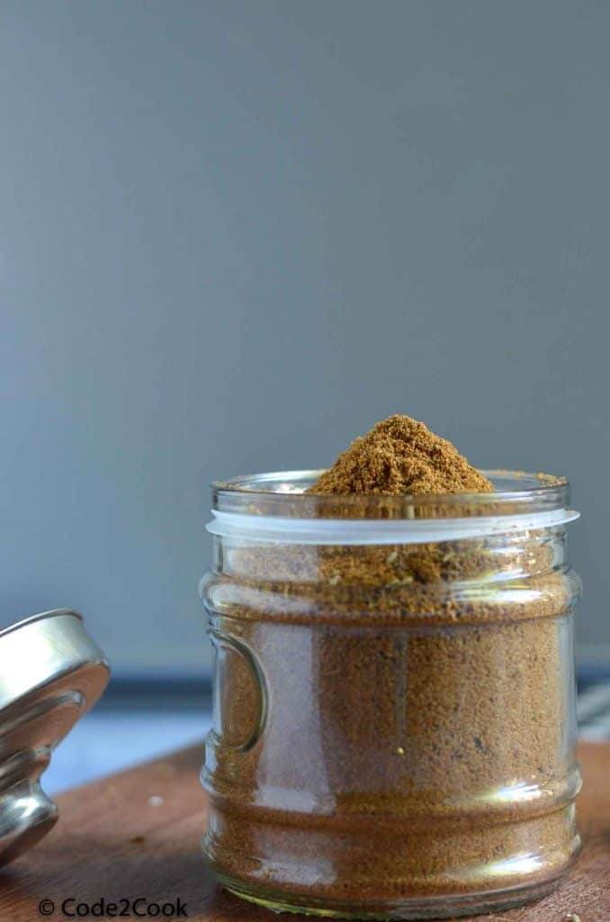 ground cumin in in a glass jar, kept on a wooden board.