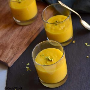 Aamras served in three small glasses and garnished with chopped nuts