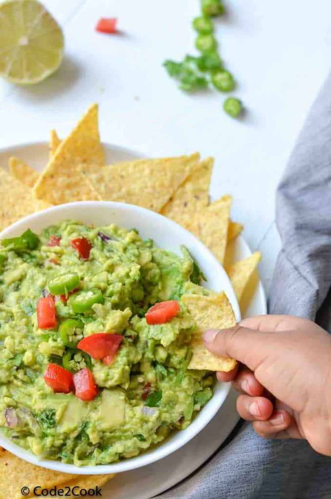 scooping simple guacamole with nacho