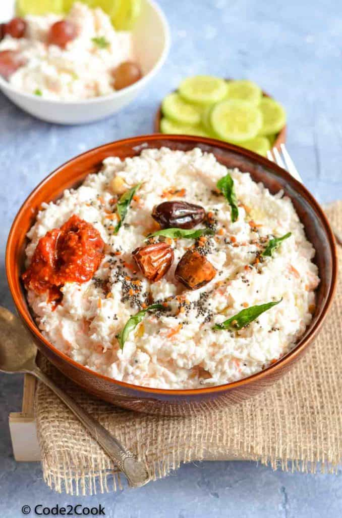 curd rice served with pickle and garnished with tempering