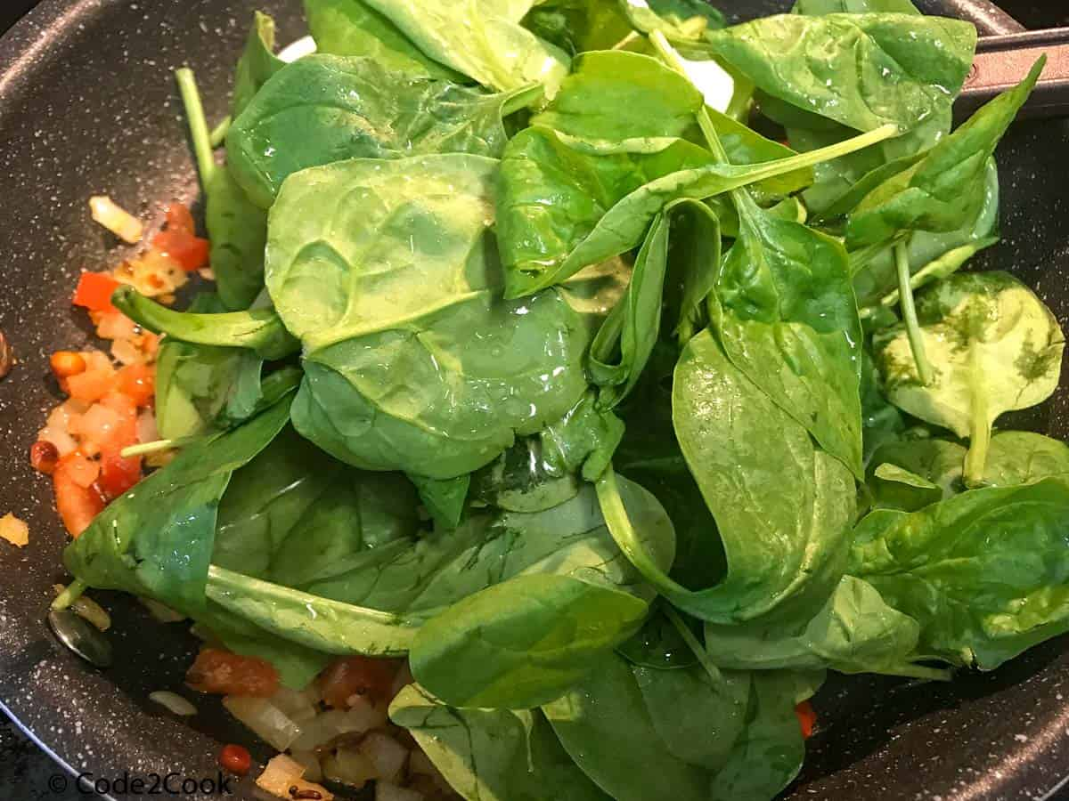 Adding spinach to the mixture.